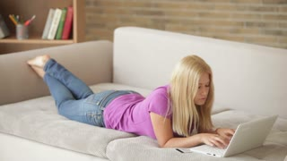 Charming blonde girl lying on couch using laptop looking at camera and smiling