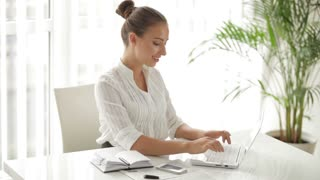 Charming businesswoman sitting at table using laptop and writing in notebook