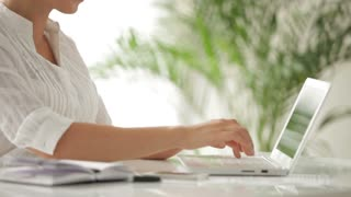 Charming businesswoman sitting at table using laptop with smile