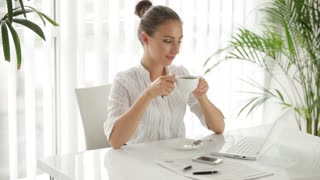Charming businesswoman sitting at table with cup of coffee