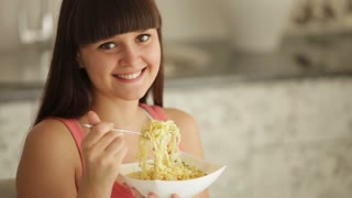 Charming girl at kitchen eating noodle and smiling