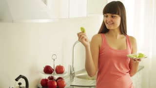 Charming girl in kitchen eating fruits and smiling at camera