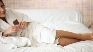 Charming girl lying in bed eating bar of chocolate looking at camera and smiling. Panning camera