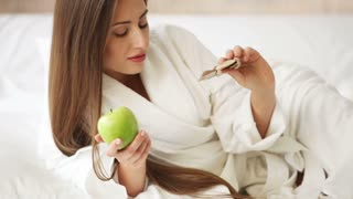 Charming girl lying in bed holding apple and bar of chocolate smiling and looking at camera. Panning camera