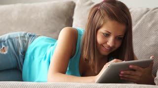 Charming girl lying on sofa using touchpad and smiling
