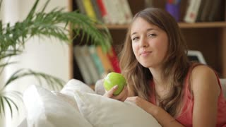 Charming girl relaxing on sofa eating apple looking at camera and smiling