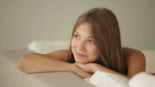 Charming girl relaxing on sofa looking at camera and smiling