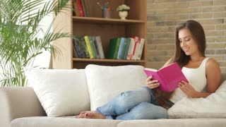Charming girl relaxing on sofa reading book and smiling at camera