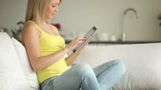 Charming girl relaxing on sofa using touchpad and smiling