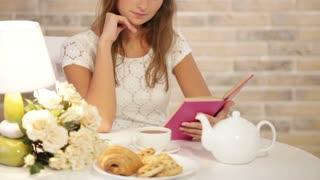 Charming girl sitting at cafe reading book looking at camera and smiling. Panning camera