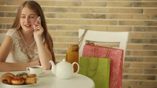 Charming girl sitting at cafe talking on mobile phone and smiling. Panning camera