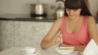 Charming girl sitting at kitchen table and eating noodle