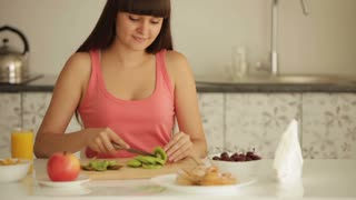 Charming girl sitting at kitchen table and slicing kiwi