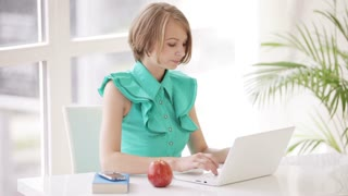 Charming girl sitting at office desk using laptop eating apple looking at camera and smiling. Panning camera