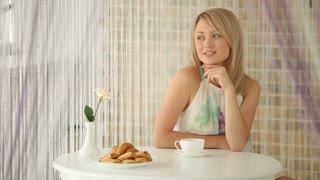 Charming girl sitting at table at cafe with cup of tea and smiling