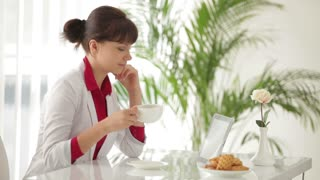 Charming girl sitting at table drinking tea and using tablet