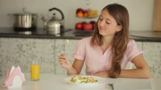 Charming girl sitting at table eating salad using touchpad and smiling at camera