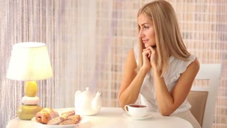 Charming girl sitting at table with cup of tea looking at camera and smiling