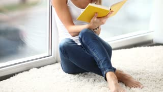 Charming girl sitting by window reading book closing it and smiling, Panning camera