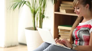 Charming girl sitting on floor using laptop looking at camera and smiling. Panning camera