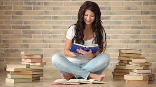 Charming girl sitting on floor with stack of books reading one and smiling at camera
