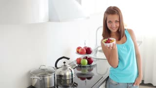Charming girl standing in kitchen and holding bowl of salad