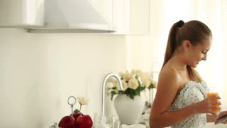 Charming girl standing in kitchen using touchpad drinking juice and smiling at camera. Panning camera