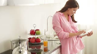 Charming girl standing in kitchen using touchpad looking at camera and smiling. Panning camera