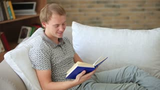 Charming guy relaxing on couch reading book looking at camera and smiling