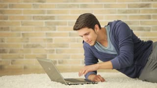 Charming guy sitting on floor and using laptop