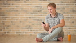 Charming guy wearing earphones sitting on floor using cell phone and smiling at camera