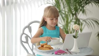 Charming little girl sitting at table with laptop drinking tea and smiling at camera