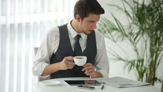 Charming man sitting at table reading newspaper and drinking coffee