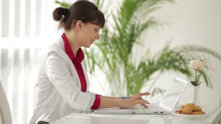 Charming woman sitting at table writing in notebook and using laptop