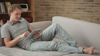 Charming young man relaxing on couch using touchpad looking at camera and smiling