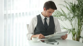 Charming young man sitting at table reading newspaper and drinking coffee