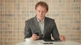 Charming young man sitting at table using mobile phone and touchpad and smiling at camera