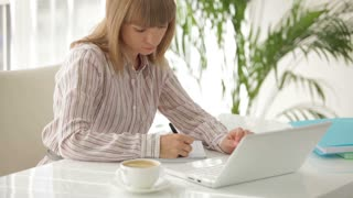 Charming young woman at office table working on laptop writing in notebook and smiling at camera