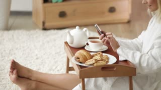Charming young woman in bathrobe sitting on floor with tray of food using mobile phone and smiling. Panning camera