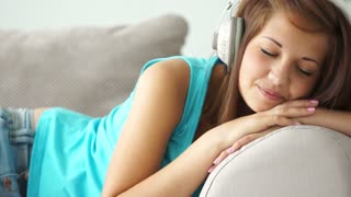 Charming young woman in headset relaxing on sofa and smiling