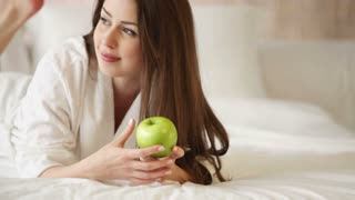 Charming young woman relaxing in bed holding green apple looking at camera and smiling. Panning camera