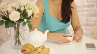 Charming young woman sitting at cafe drinking tea looking at camera and smiling. Panning camera