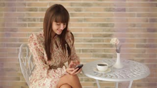 Charming young woman sitting at cafe using cellphone and drinking tea