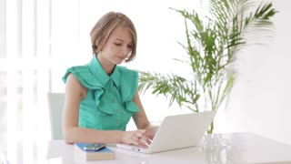 Charming young woman sitting at desk using laptop looking at camera and smiling. Panning camera