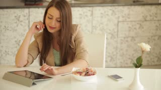 Charming young woman sitting at kitchen table with touchpad eating fruit salad and smiling at camera
