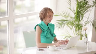 Charming young woman sitting at office desk using laptop closing it looking at camera and smiling. Panning camera