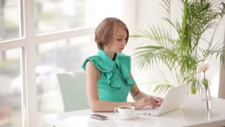 Charming young woman sitting at office desk with cup of coffee using laptop looking at camera and smiling