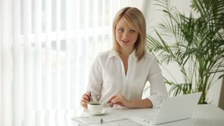 Charming young woman sitting at table with laptop stirring coffee and smiling