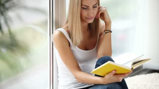 Charming young woman sitting by window reading book and smiling. Panning camera