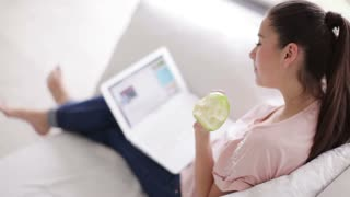 Charming young woman sitting on couch with laptop holding apple and smiling at camera